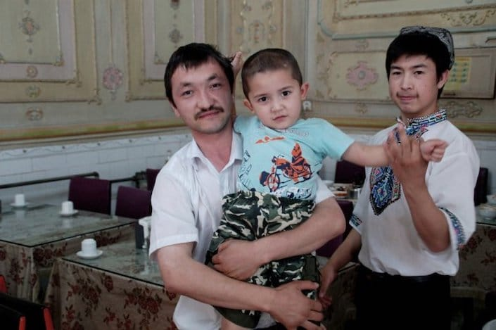 two Uyghur men, one of whom is holding a little boy, inside a restaurant in China