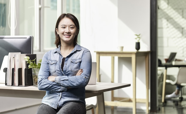 portrait of a young asian business woman looking at camera smiling arms crossed