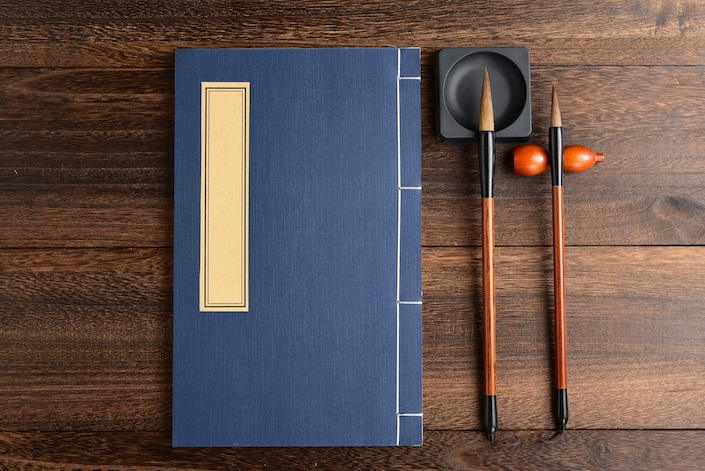chinese notebook and calligraphy pens on wooden table
