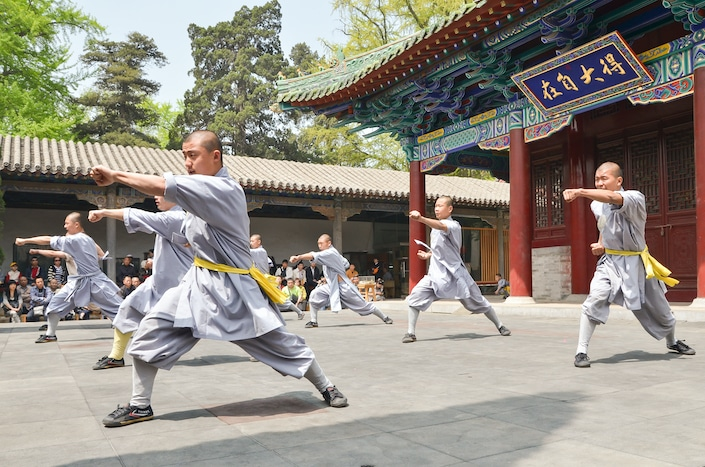 several Chinese monks in grey garments with yellow scarves around their waists practicing Chinese martial arts in front of a traditional Chinese building
