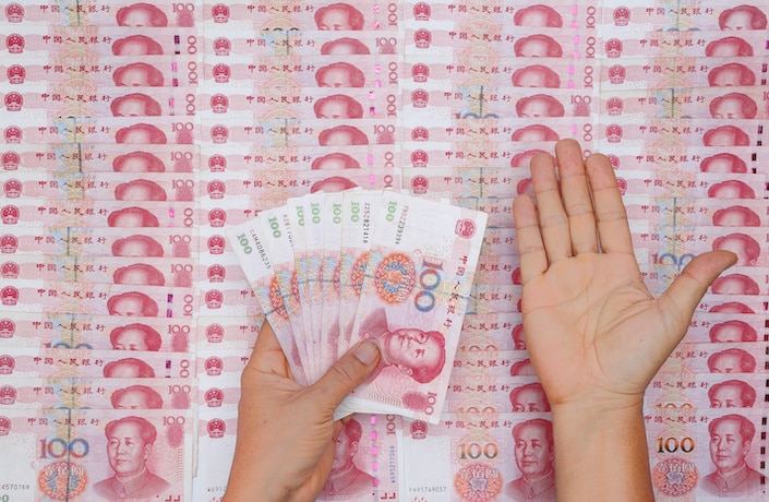 chinese currency neatly spread out on table with person's open hand above