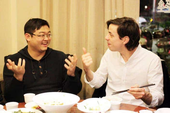 western man and chinese man chatting while eating dinner