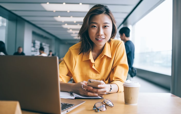 Cheerful Asian female professional in yellow blouse using smartphone and looking at camera at desk with laptop