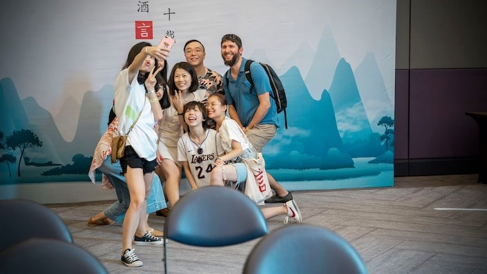 group of young professional taking selfie in front of a backdrop with silhouette of karst mountains