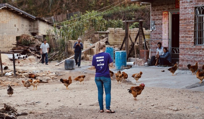 western woman standing in chinese village with back to camera and chickens walking around her