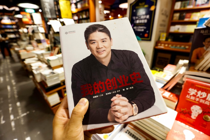man holding book in Chinese bookstore of Liu Qiangdong