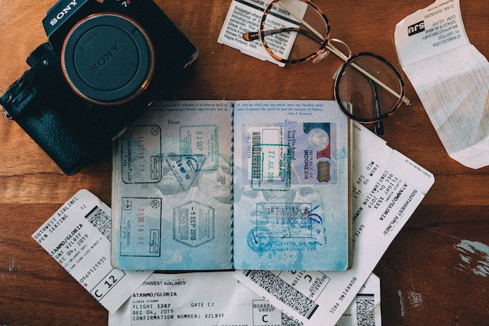 passport, camera, plane tickets and eyeglasses on wooden table