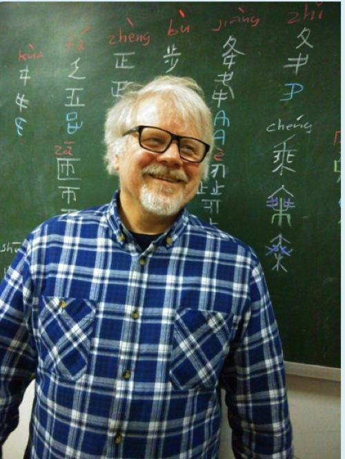 older man with white hair and goatee in front of blackboard with chinese characters