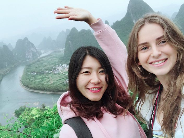 selfie of two young women with big smiles in front of karst mountains and a river