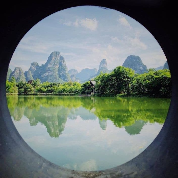 view of karst guilin mountains with water in foreground through circular pipe