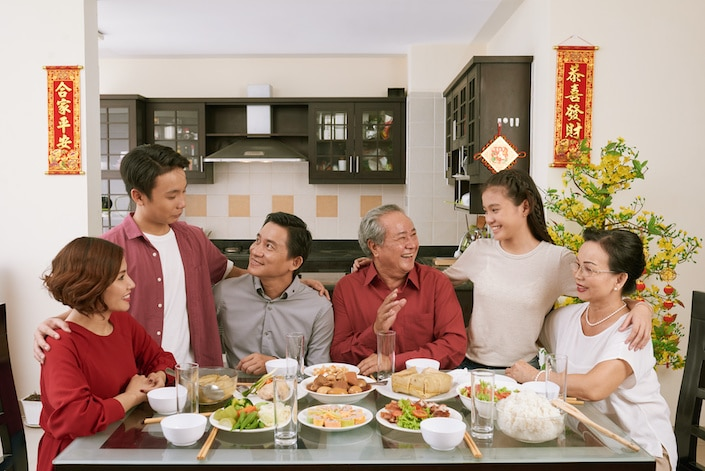 Chinese family gathered around the dining room table at home