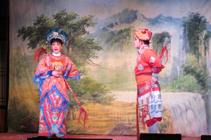 two chinese opera performers in front of a landscape oil painting