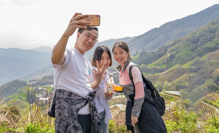 a young chinese man and two chinese young ladies taking a selfie in rice terraces in china