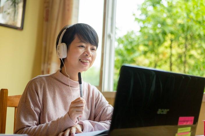 chinese tutor teaching student using her laptop