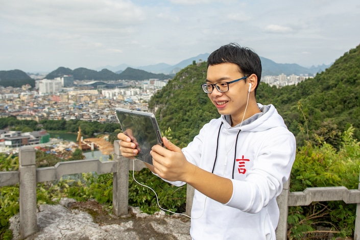 chinese teacher teaching chinese online while holding ipad at a park in china with mountains in the background