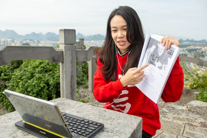 chinese teacher sitting outdoors holding textbook toward her laptop to show her online student something in the book