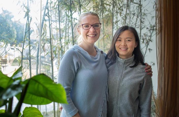 student and teacher in china with plant in foreground and bamboo in background