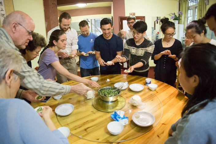 a group of young people standing around a round wooden table making chinese dumplings