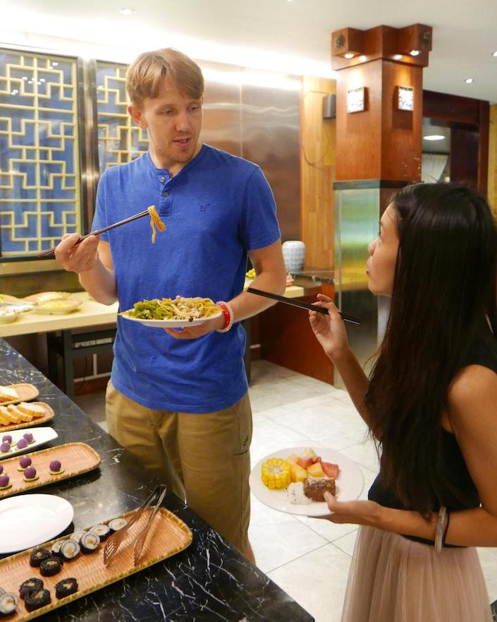 a young western man and a young chinese lady standing, eating and chatting at a restaurant in china