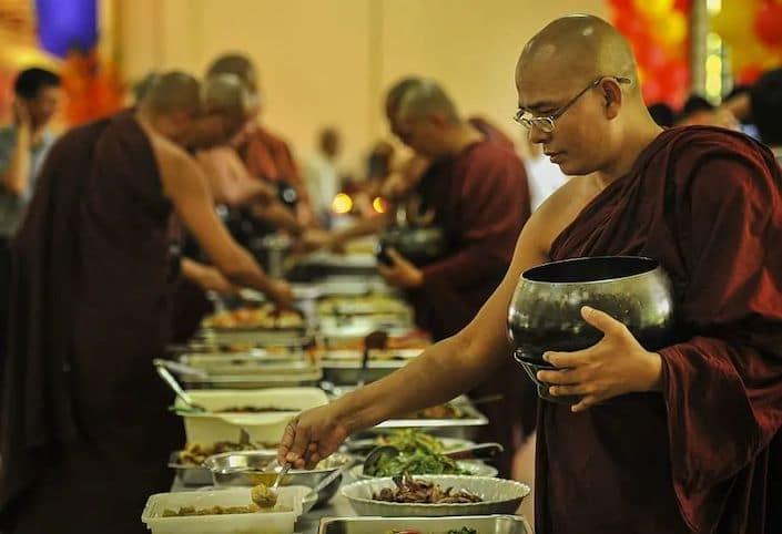 buddhist man getting food at a vegetarian buffet