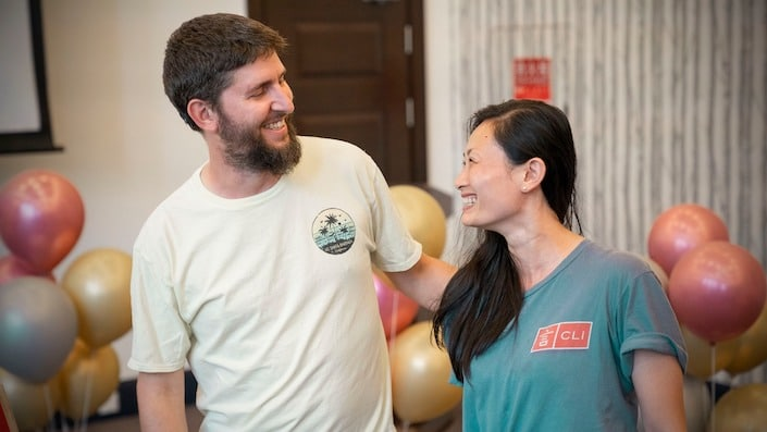 a man with a beard and a chinese woman looking and smiling at each other with balloons in the background