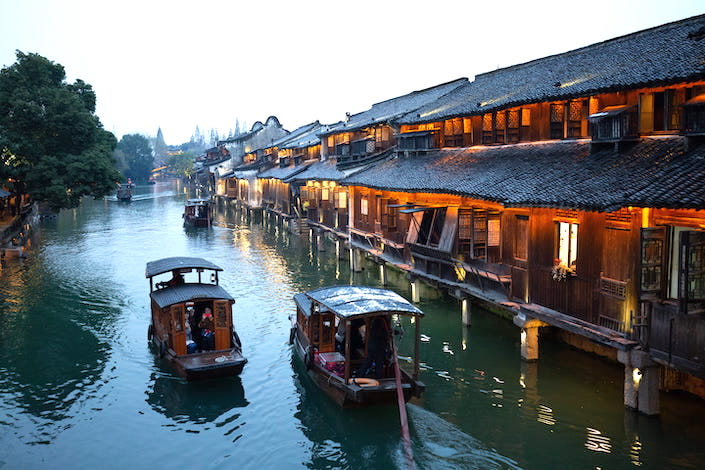 two small wooden boats floating down a canal in wuzhen, china near wooden homes and stores