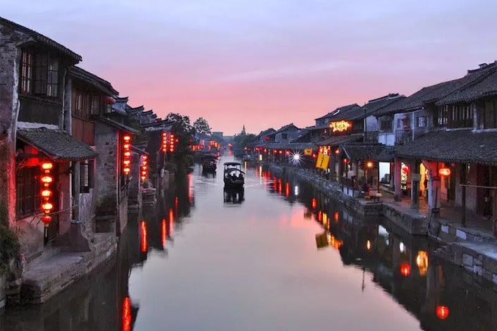 tranquil canal between ancient wooden chinese structures with red lanterns glowing in the water below