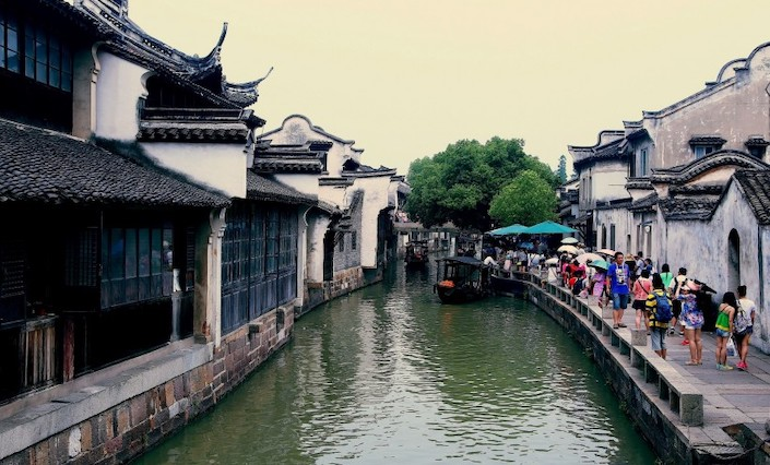 canal in between ancient chinese architecture with tourists walking alongside