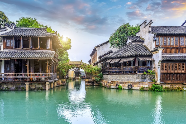 blue-green water in front of old wooden chinese structures in wuzhen water town