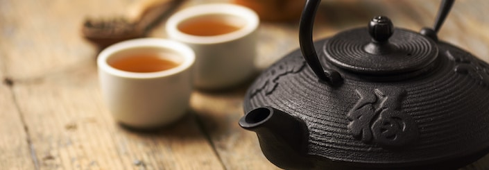 Traditional Chinese herbal tea recipe prepared in cast iron teapot with organic dry herbs